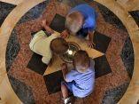 Imagen tomada en el Capitolio de La Habana donde tres niños observan una la réplica del diamante que marca el kilómetro cero de todas las carreteras de Cuba. Foto: Tony Hernández Mena
