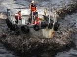 Buzos se trasladan en el Golfo de México en aguas completamente contaminadas de petróleo.