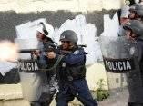 Un agente de la brigada antidisturbios dispara gases lacrimógenos contra los partidarios del presidente de Honduras José Manuel Zelaya, en un esfuerzo por alejarlos de los alrededores de la Embajada de Brasil, en Tegucigalpa
