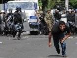 Uno de los protestantes a favor del presidente Zelaya es perseguido por la policía hondureña durante los disturbios cerca de la embajada de Brasil en Tegucigalpa, Honduras, el 24/09/2009.