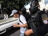 Oficiales de escuadras antimotines arrestan a un seguidor del presidente Zelaya durante disturbios alrededor de la embajada de Brasil en Tegucigalpa, Honduras, el 24/09/2009.
