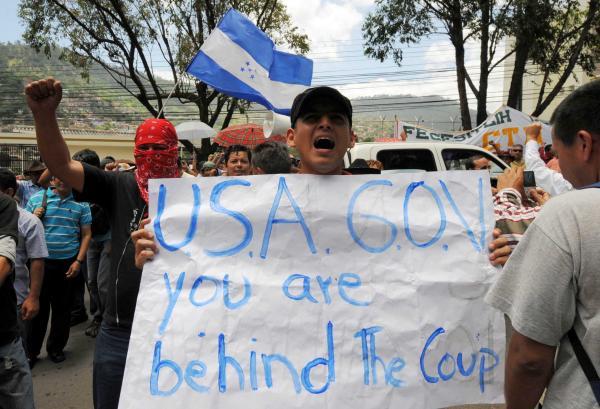 Un hombre porta cartel y grita consignas demandando la restitución del presidente Manuel Zelaya durante una demostración en las afueras de la embajada de los Estados Unidos en Tegucigalpa, Honduras el 14 de julio de 2009. FOTO/Orlando SIERRA/AFP