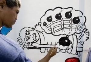 """Un joven dibuja en la pared una caricatura de Posada Carriles, que se refiere a sus palabras después de dirigir los atentados con bombas a hoteles de Cuba: """"duermo como un bebé""""."""