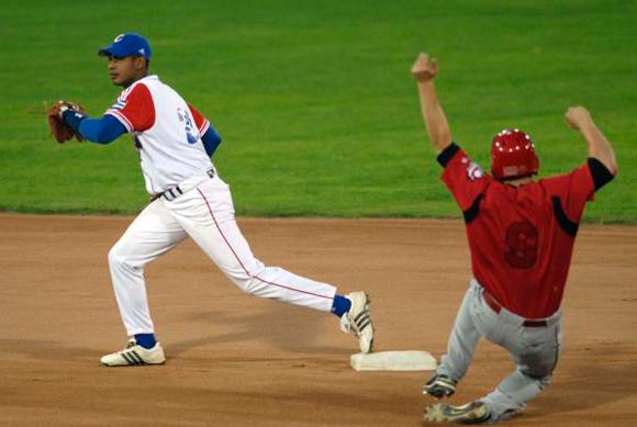 Hector Olivera (blanco), haciendo jugada en segunda base