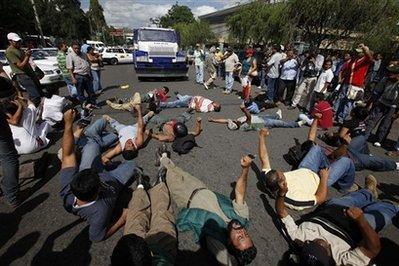 Seguidores del presidente Manuel Zelaya gritan consignas acostados en el suelo en Tegucigalpa. (Foto AP)
