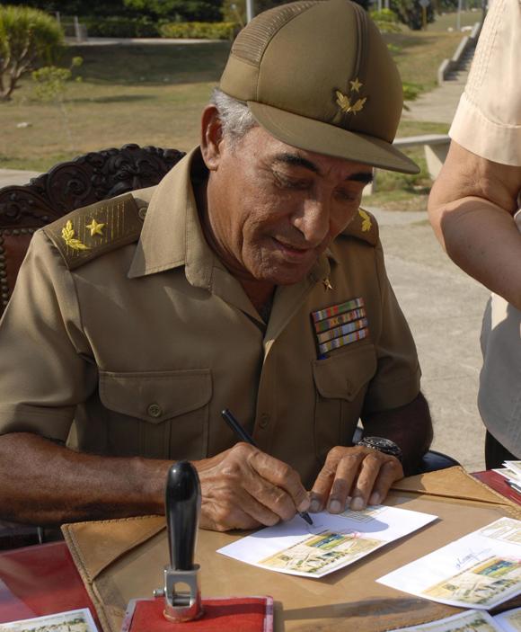 El General de brigada Arnaldo Tamayo Méndez, primer cosmonauta de América Latina y el Caribe, realiza la cancelación de un sello postal.