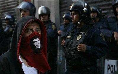 """Una manifestante enmascarada con una imagen Ernesto """"Che"""" Guevara, pasa delante de la policía  durante una marcha, este 2 de octubre, en conmemoración de la matanza estudiantil de 1968 en Ciudad de México. En esa fecha, hace 41 años, el ejército mexicano abrió fuego contra una manifestación estudiantil y mató al menos a unos 350 jóvenes, hecho considerado un genocidio por la Justicia mexicana. (Foto: AP / Marco Ugarte)"""