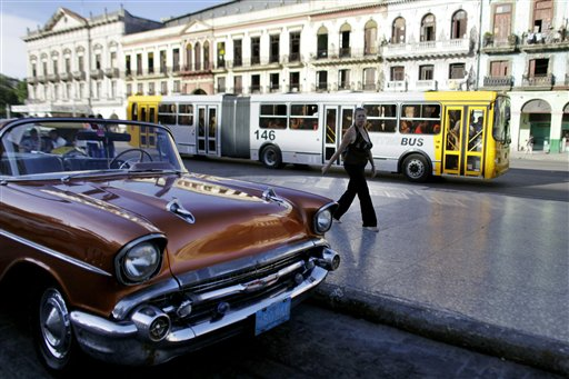 """Uno de los nuevos autobuses articulados que reemplazaron a los vetustos """"camellos"""" en La Habana. Los modernos buses comparten las calles con viejos autos de los año 50. (AP Photo/Javier Galeano)"""