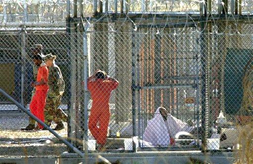 Una foto de archivo del 15 de marzo de 2002 muestra a un prisionero del Campo Rayos X, escoltado por guardias, mientras otros reclusos están en sus celdas en la Base Naval de la Bahía de Guantánamo, en Cuba. (Foto AP/Tomas van Houtryve)