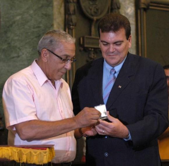 Juan Formell (I), director de los Van Van, recibe de manos de Gustavo Cobreiro, rector de la Universidad de La Habana (UH), la Placa Conmemorativa Aniversario 280 de la UH , otorgada a dicha orquesta, en el Aula Magna de la universidad, el 29 de octubre de 2009.