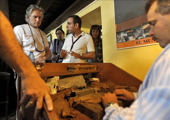 """El actor estadounidense Michael Douglas (i) observa a un tabaquero """"torciendo"""" un puro hoy, 27 de octubre de 2009, durante un recorrido por el centro histórico de la Habana Vieja (Cuba). EFE"""