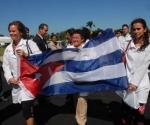 """Brigada """"Ernesto Che Guevara"""", compuesta por 240 Médicos, Intensivistas y Estomatólogos, con rumbo a Venezuela, donde cumplirá misión en Barrio Adentro, portan la bandera cubana en el acto de despedida, realizado en el aeropuerto Internacional José Martí, en La Habana, el 08 de octubre de 2009. Foto: Oriol de la Cruz/AIN"""