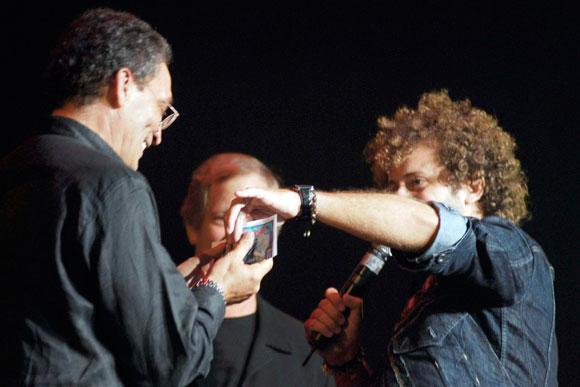 Raúl Paz, cantautor cubano, entrega un cheque con el dinero recaudado para las escuelas afectadas por los huracanes a José Juan Ortiz, representante de la UNICEF en Cuba