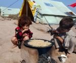 Niños paquistaníes comen en un campo de desplazados a las afueras de Peshawar. Más de mil millones de personas padecen hambre en el mundo. - AFP