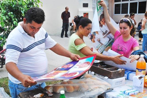 Promotora de la salud(D), en la distribución de afiches, con motivo de las actividades en saludo al Día Mundial de Lucha contra el VIH/SIDA, en Las Tunas
