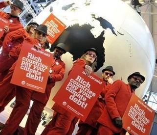 """Activistas medioambientales de la organización danesa MS ActionAid muestran pancartas que dicen """"Los países ricos tienen que pagar su deuda climática"""". Los indios del Amazonas, los agricultores de Malawi, los monjes tibetanos y los inuit de Groenlandia intercambiaron este miércoles ideas sobre cómo combatir el calentamiento global en un foro alternativo bullicioso en Copenhague en el marco de negociaciones de la ONU. (AFP / Attila Kisbenedek)"""