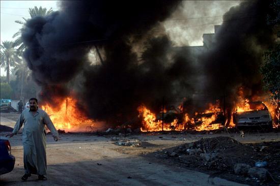 Un habitante se aleja de varios vehículos en llamas tras la explosión de un coche bomba cerca de la zona internacional en el centro de Bagdad (Irak) hoy, martes, 15 de diciembre de 2009. Foto EFE/Shehab Ahmed.