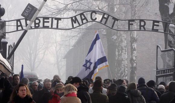 Visitantes de todo el mundo pasan bajo el cartel de Arbeit Macht Frei (el trabajo libera) sobre la puerta principal del campo de exterminio nazi en Auschwitz, miércoles 27 de enero de 2010, horas antes de las solemnes ceremonias del 65to aniversario de su liberación por el Ejército Rojo. (AP Foto/Czarek Sokolowski).