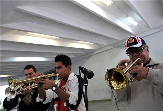 El Guajiro Mirabal (d), integrante del Buena Vista Social Club, toca junto a un grupo de jóvenes músicos hoy, martes 5 de enero de 2010, durante una presentación de la orquesta en la Escuela Nacional de Arte de La Habana (Cuba). EFE/Alejandro Ernesto