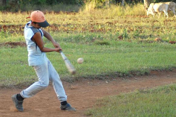 Muchachos jugando pelota de placer o maniguera, en Yaguajay, Sancti Spíritus, Cuba.