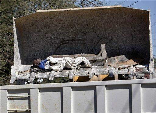 Foto: Una topadora suelta el cuerpo de René Morancy en un camión de volquete mientras cuadrillas de operarios retiran los cadáveres de las calles de Puerto Príncipe, el viernes 15 de enero de 2010, luego del terremoto que devastó la capital de Haití el martes. (Foto AP/Gerald Herbert)