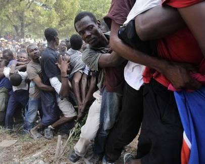 Haitianos luchan por permanecer en fila para obtener ayuda que reparte en Puerto Príncipe la 82 división aerotransportada de Estados Unidos. Foto Ap