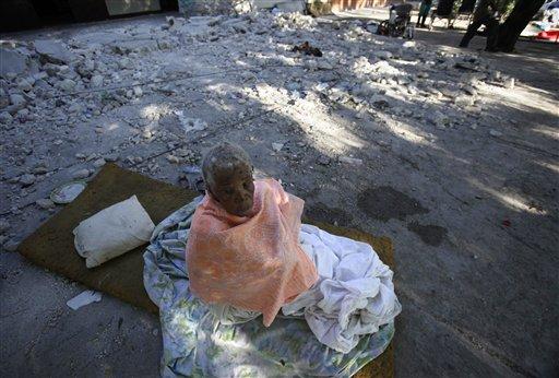 Una mujer está sentada sobre escombros de su asilo de ancianos, dañado por el terremoto del jueves, en Puerto Príncipe, domingo 17 de enero de 2010. Más de 100 ancianos están viviendo frente los vestigios de un asilo sin comida ni cuidados distintos a un eventual baño que dos enfermeros que quedaron para ayudarlos les dan. (AP Foto/Julie Jacobson)
