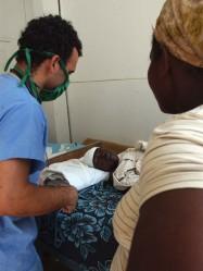El médico cubano Carlos Placencia Reyes atiende a un herido. Hospital del Seguro Social I Ofatma en Puerto Principe, Haití. AIN Foto: Juvenal BALAN /Periódico Granma /Enviado Especial