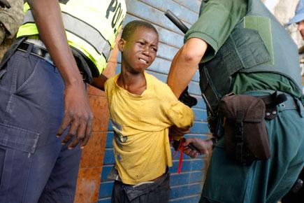 En la imagen, policías detienen a un niño acusado de saqueo. Foto Reuters