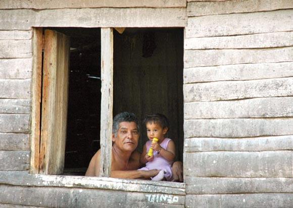 Una pequeña junto a su papá nos observan desde una ventana de su casa. Foto: Kaloian