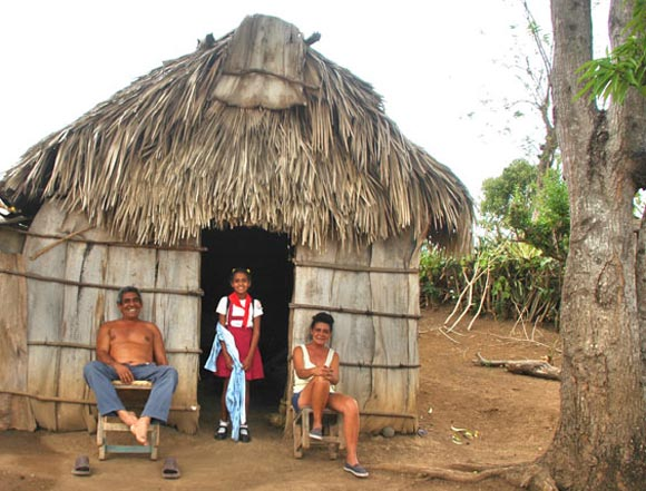 Una pionera junto a sus papás sonríe a nuestro paso por cerca de su casa, en medio de la Sierra Maestra. Foto: Kaloian