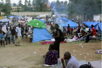 En el campo de fútbol de Jacmel se refugian 3 200 personas que quedaron sin hogar. Allí se organizan en cocinas colectivas, los hombres rajan leña y cargan los sacos con alimentos que llegan de las ayudas, los niños hacen la cola del agua y juguetean por  el lugar.