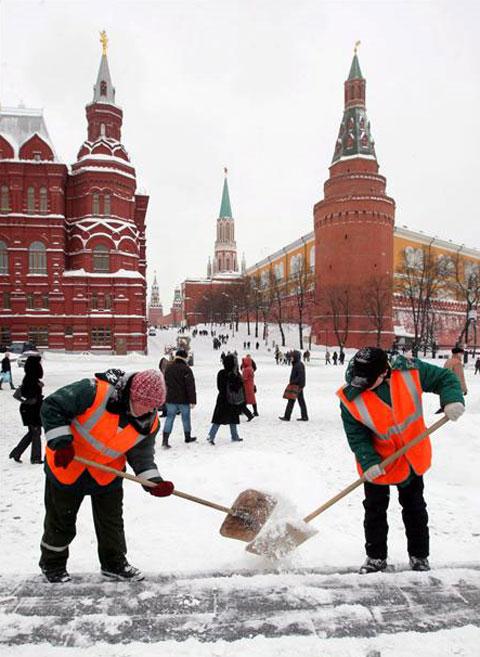 Dos trabajadores despejan la plaza cercana al Kremlin en Moscú, Rusia, tras una fuerte nevada, lunes, 22 de febrero de 2010. EFE Foto: Sergei Chirikov