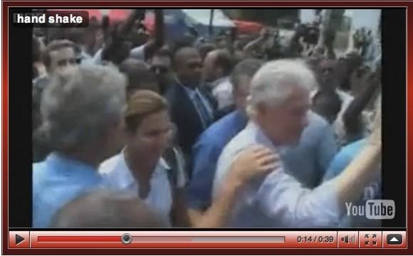 Bush se limpia la mano después de saludar a un haitiano.