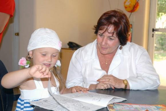 La pequeña Sofía muestra sonriente su cuaderno a la doctora Xenia Autor: Juan Luis Aguilera