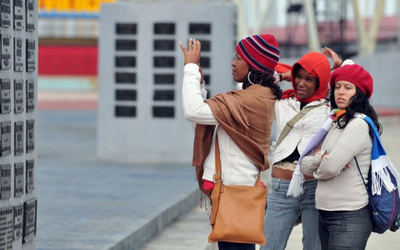 Tres jóvenes fotografían una de las columnas de la Tribuna Antimperialista José Martí, frente al Malecón habanero