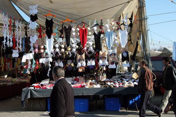 Un bazar callejero en el cual se ofrecen múltiples sostenes de mujer.