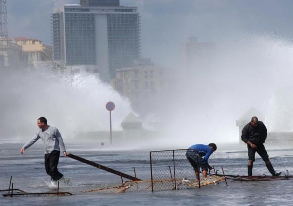 Trabajadores de viales colocan vallas de contencion del transito durante la penetración del mar en el Malecón de La Habana, Cuba, el 3 de marzo de 2010. El Centro de Pronósticos, del Instituto de Meteorología de Cuba, anunció que estas inundaciones en la costa norte occidental de Cuba obedecen al paso de un frente frío. AIN Foto: Sergio Abel REYES REINOSO