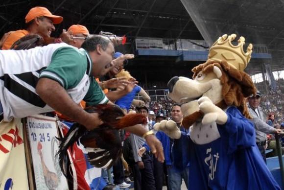 La mascota de Industriales (D), con fanáticos spirituanos durante el juego donde los Leones de Industriales tomaron la delantera en el play off (2x1), contra los Gallos de Sancti Spíritus, al vencerlos 6x4, en el estadio Latinoamericano, en Ciudad de La Habana, el 3 de marzo de 2010. AIN FOTO/Marcelino VAZQUEZ HERNANDEZ