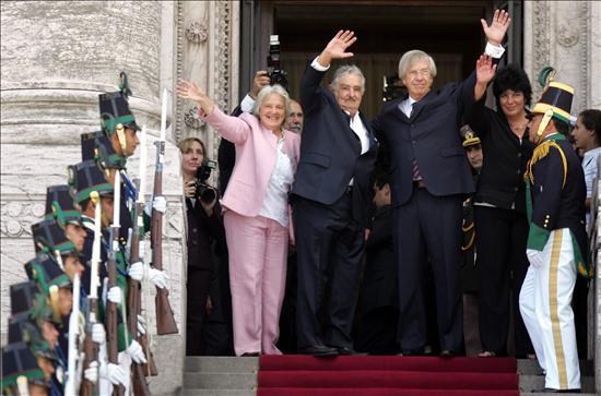 El presidente electo José Mujica (c), saluda junto a su esposa, la presidenta de la Asamblea Legislativa Lucía Topolansky (i), y el vicepresidente electo Danilo Astori (d), hoy, lunes 1 de marzo de 2010, desde la escalinata del Palacio Legislativo, en Montevideo (Uruguay), donde Mujica prometerá acatar la Constitución. EFE/Iván Franco