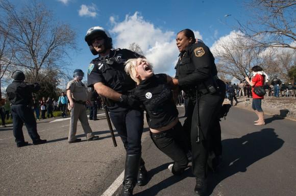 Dos policías se llevan a rastras a la estudiante Laura Mitchell como los estudiantes demuestran en Davis el jueves. Los estudiantes trataron de marchar hacia la carretera interestatal 80, pero fueron detenidos por agentes de la paz de varios organismos como la Policía de Davis, alguacil del condado de Solano, y la cogeneración.