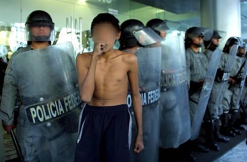 Muchos adictos a los inhalables no reciben atención de ninguna de las autoridades. En la imagen, un menor se droga frente a elementos policiacos que custodian un edificio. Foto: Jesús Villaseca