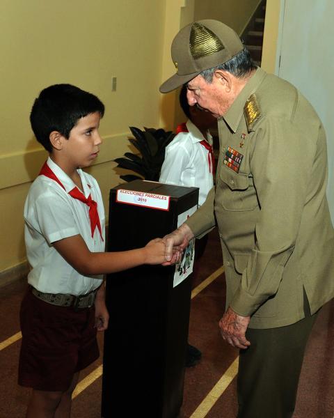Raúl saluda a los pioneros que custodian la urna, tras ejercer su derecho al foto Foto: Raúl Abreu/AIN