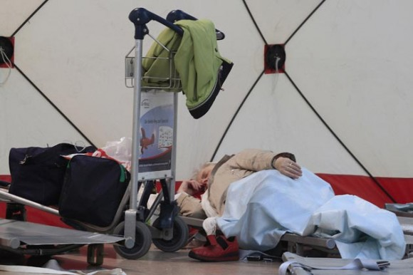 Foto: Pasajeros descansan en camas de acampar, mientras esperan la reapertura de los vuelos en el aeropuerto de Frankfurt. FP PHOTO DDP/TORSTEN SILZ GERMANY OUT