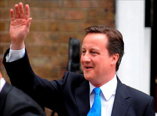 """El líder del Partido Conservador británico, David Cameron, saluda a sus votantes a su llegada a una comparecencia en Londres, (Inglaterra), hoy, viernes, 7 de mayo e 2010. David Cameron hizo hoy una oferta de gobierno a los liberaldemócratas de Nick Clegg, en la que se muestra dispuesto a abordar temas cruciales para la tercera formación del país, como la reforma del sistema electoral. Cameron, ganador sin mayoría absoluta de las elecciones generales celebradas ayer en el Reino Unido, destacó la importancia de formar un """"gobierno estable pronto"""" por el bien del país. EFE/Andy Rain"""