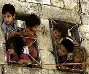 Niños palestinos asomados a una ventana