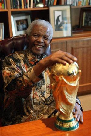 En esta foto distribuida por la Fundación Mandela, el ex presidente sudafricano Nelson Mandela sonríe junto con el trofeo de la Copa del Mundo el jueves, 6 de mayo de 2010, en Johanesburgo.(AP Photo/Mandela Foundation)