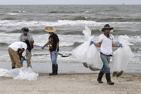 Trabajadores limpian el derrame de petróleo sin máscaras