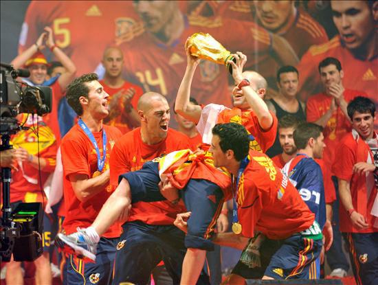 Los jugadores de la selección española de fútbol levantan a Andrés Iniesta (c) durante la celebración en el Puente del Rey, en Madrid, por la victoria en el Campeonato del Mundo de Sudáfrica 2010. EFE/Luca Piergiovanni.