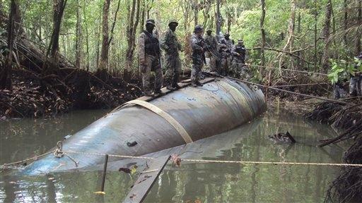 Soldados ecuatorianos aparecen sobre un submarino capturado en la selva el sábado 30 de julio, 2010. Funcionarios de la FEA estadounidense dicen que la nave hallada cerca de la frontera con Colombia podría transportar toneladas de cocaína.